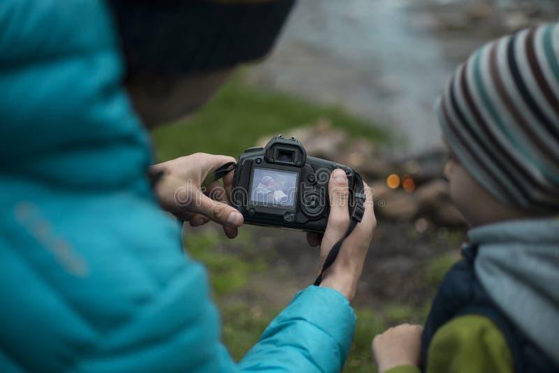 Adolescent s'asseyant près d'un feu de camp à un terrain de camping, et regards dans l'appareil-photo photo libre de droits