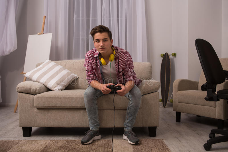 Adolescent s'asseyant sur le sofa jouant des jeux d'ordinateur photos stock