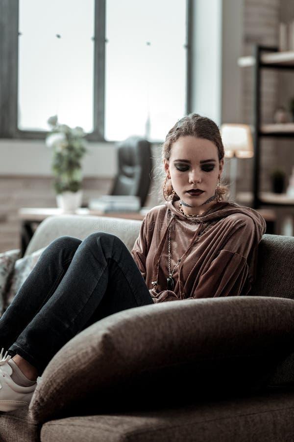 Adolescent s'asseyant sur le sofa se sentant très déprimé après école images stock