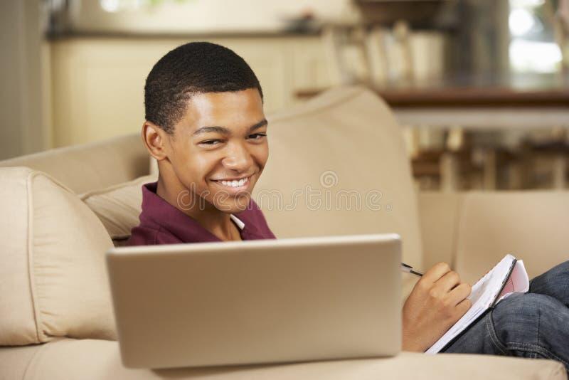 Adolescent s'asseyant sur Sofa At Home Doing Homework à l'aide de l'ordinateur portable photos stock