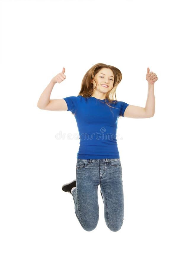 Adolescent sautant avec des pouces  photos stock