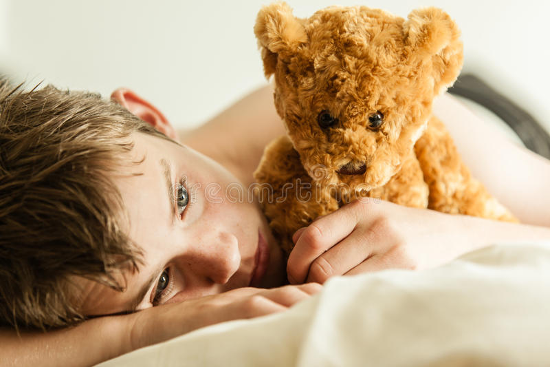 Adolescent se blottissant sur le lit avec Brown Teddy Bear images libres de droits