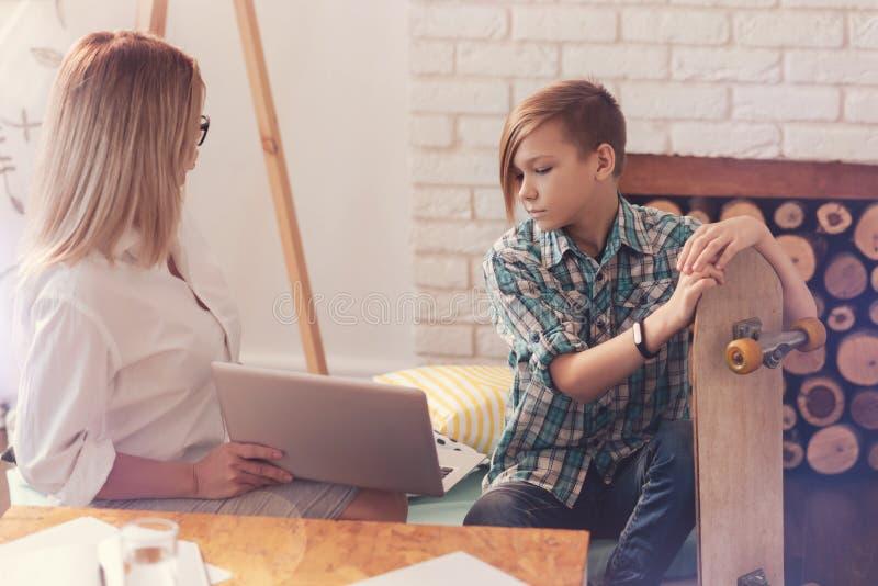 Adolescent sombre parlant avec un psychologue photographie stock