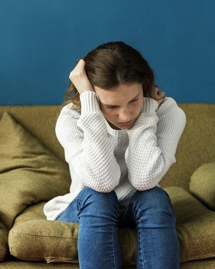 Adolescent soumis à une contrainte s'asseyant sur un sofa image stock