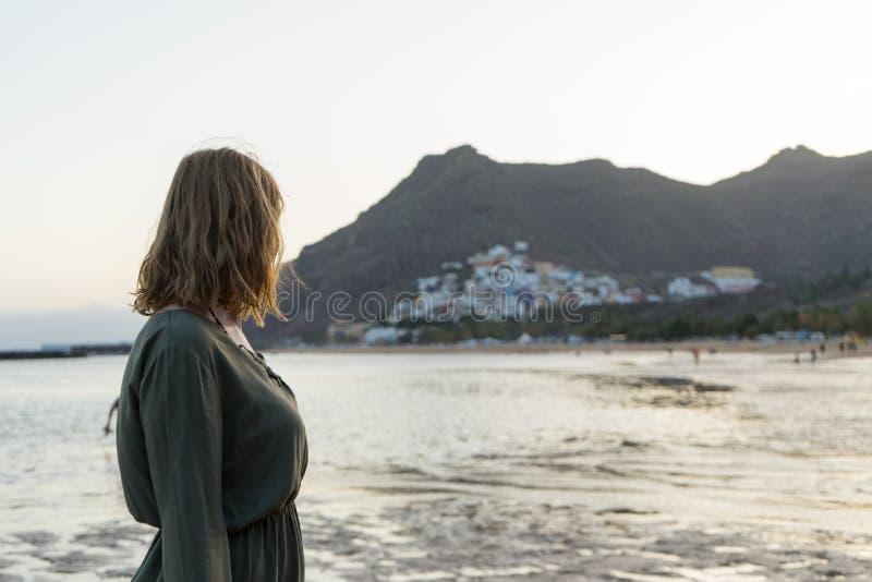 Adolescent spirituel en robe verte, admirez le coucher du soleil et la ville de mer sur une colline à Tenerife Une romantique blo photos libres de droits