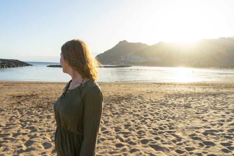 Adolescent spirituel en robe verte, admirez le coucher du soleil et la ville de mer sur une colline à Tenerife Une romantique blo photo stock