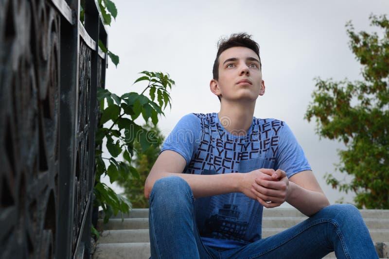 Adolescent sur des escaliers sur la rue photo stock