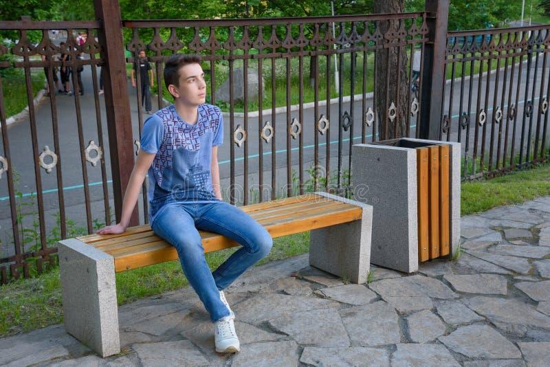 Adolescent sur le banc sur la rue photo libre de droits
