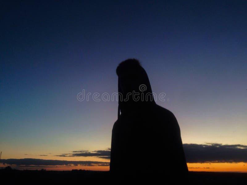 Adolescent sur le fond de coucher du soleil photo stock