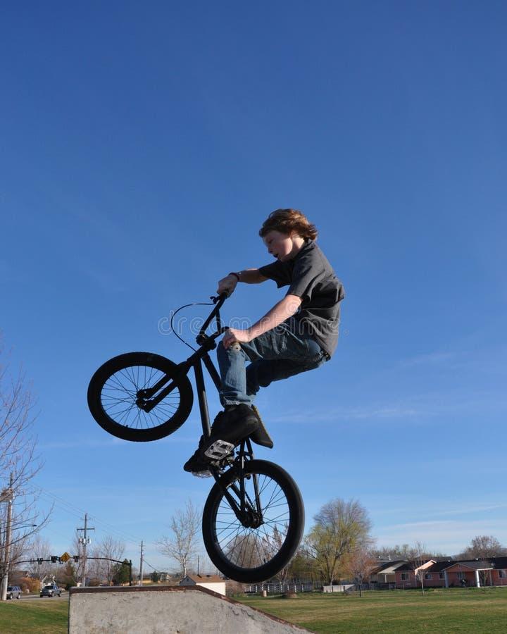 Adolescent sur le vélo de BMX dans le ciel photo libre de droits