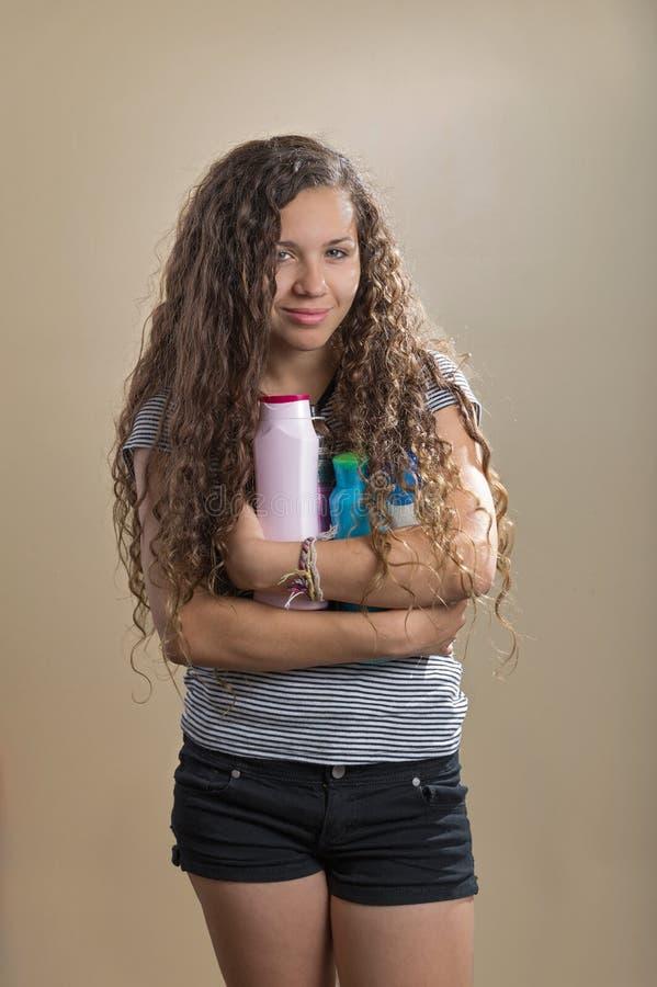Adolescent tenant des produits capillaires images stock