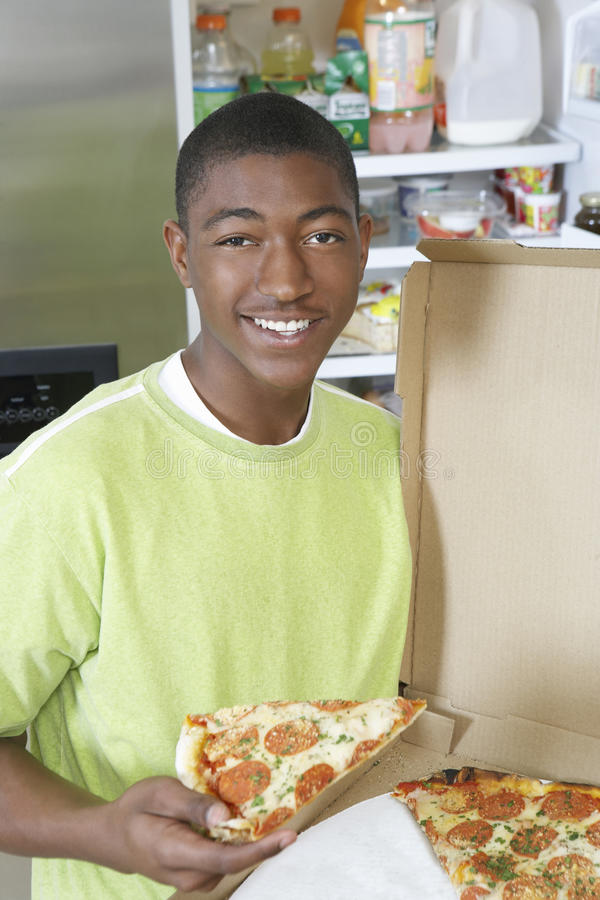 Adolescent tenant un morceau de pizza images stock