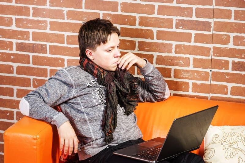 Adolescent travaillant sur l'ordinateur portable Concentration et calme photographie stock libre de droits