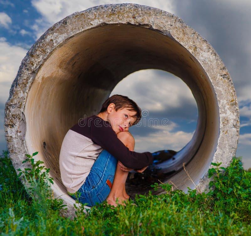 Adolescent triste de garçon sans abri s'asseyant dans le béton photos stock