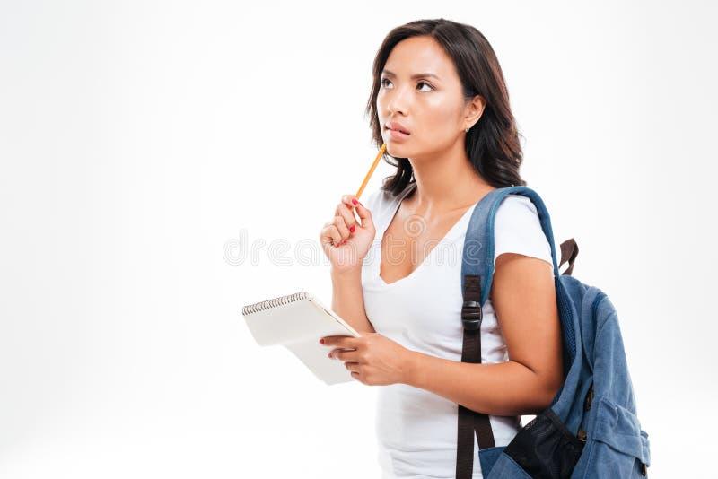 Adolescent vietnamien mignon songeur tenant l'annd de carnet pensant à quelque chose image stock