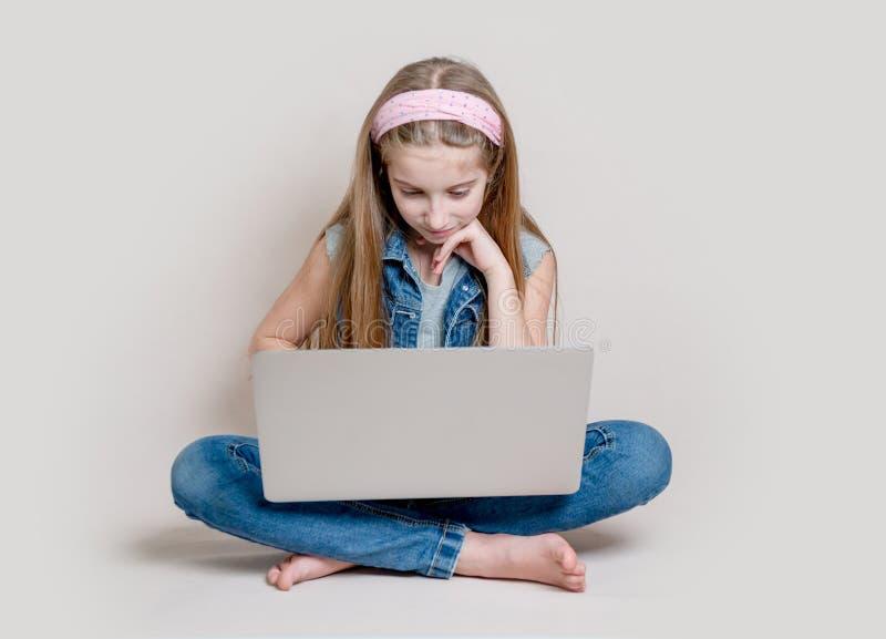 Adolescente à l'aide de l'ordinateur portable se reposant sur le plancher images stock
