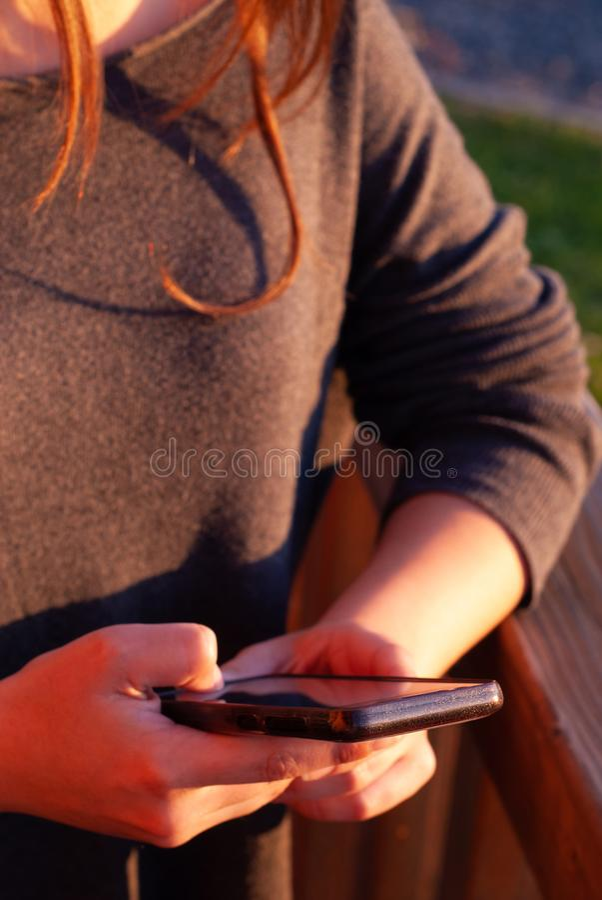 Adolescente à l'aide du téléphone intelligent mobile extérieur photos stock