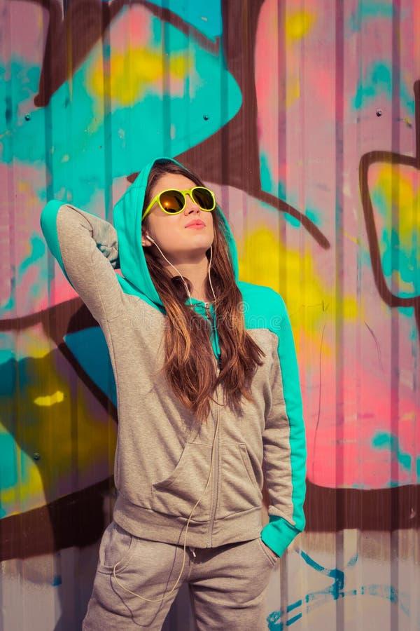 Adolescente à moda nos óculos de sol coloridos que levantam perto do fragmento fotografia de stock