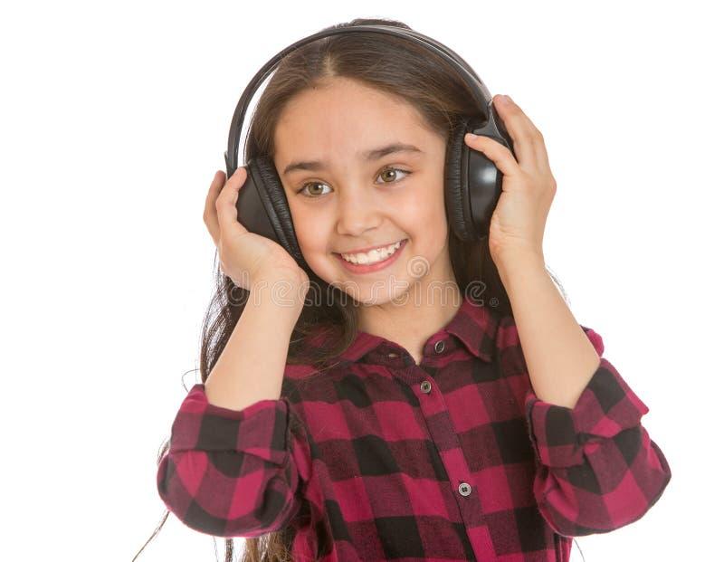 Adolescente écoutant de grands écouteurs noirs image stock