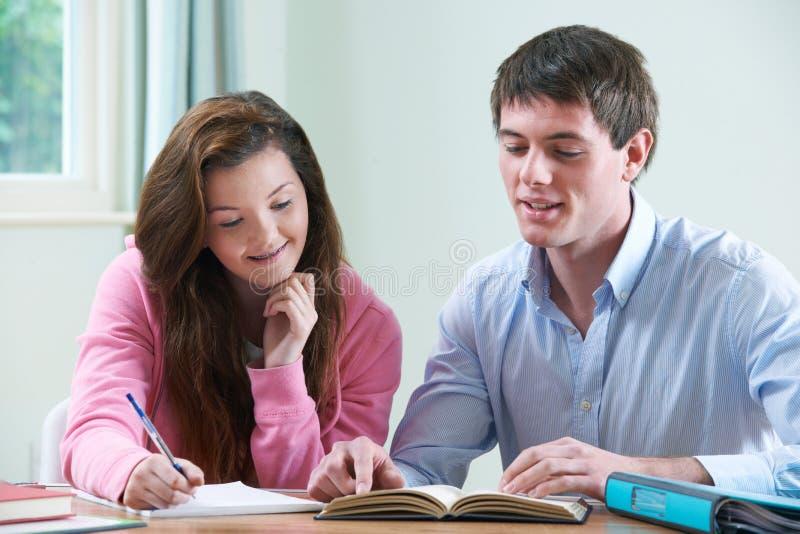 Adolescente étudiant avec le tuteur à la maison images stock