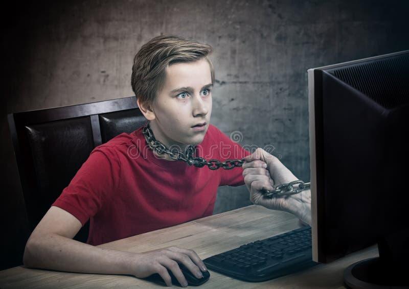 Adolescente acorrentado a seu computador fotografia de stock