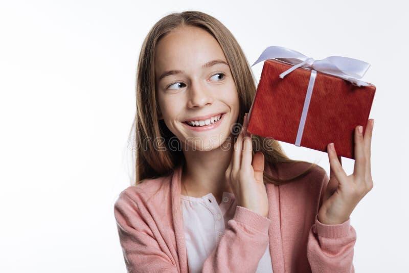 Adolescente adorável que olha a caixa com presente foto de stock