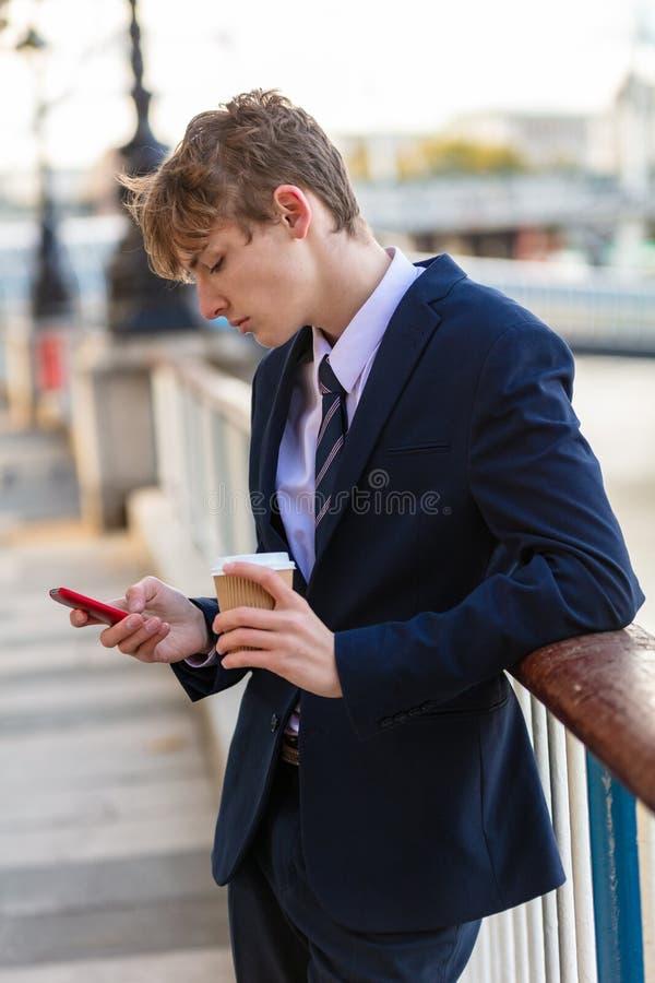 Adolescente adulto novo masculino que usa o café bebendo do telefone celular imagens de stock royalty free