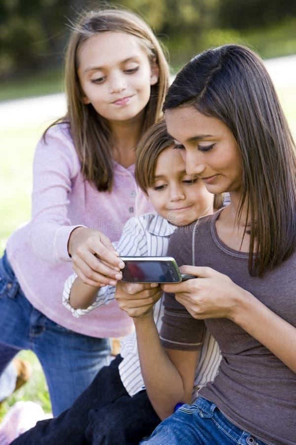 Adolescente affichant le téléphone portable aux enfants de mêmes parents image libre de droits