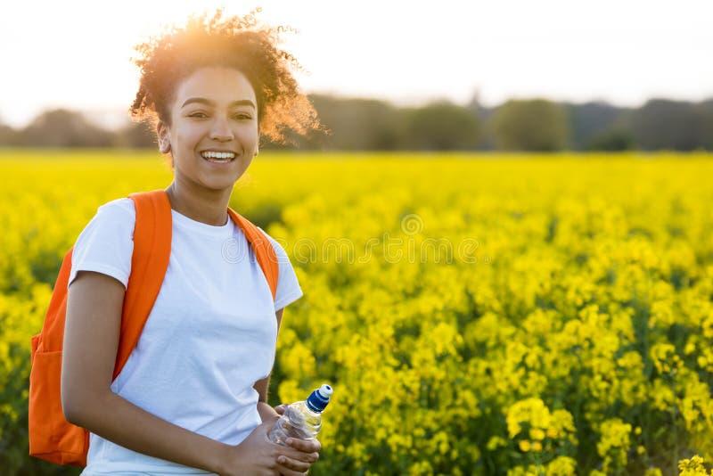Adolescente afro-americano da menina da raça misturada em flores amarelas em S fotografia de stock