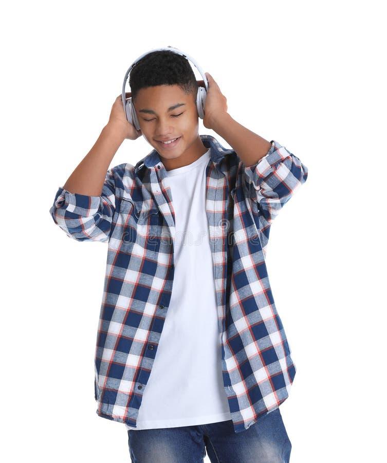 Adolescente afro-americano que escuta a música com os fones de ouvido no branco fotografia de stock royalty free