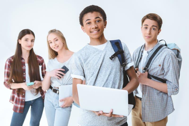 adolescente afro-americano que guarda o portátil quando amigos que estão próximo perto imagens de stock royalty free