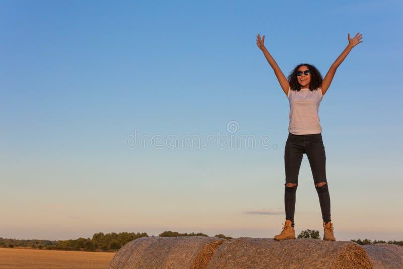 Adolescente afroamericano della ragazza della corsa mista che celebra su Hay Bal immagine stock libera da diritti