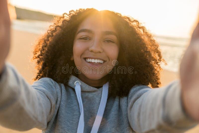 Adolescente afroamericano della ragazza della corsa mista che prende Selfie sulla spiaggia fotografia stock
