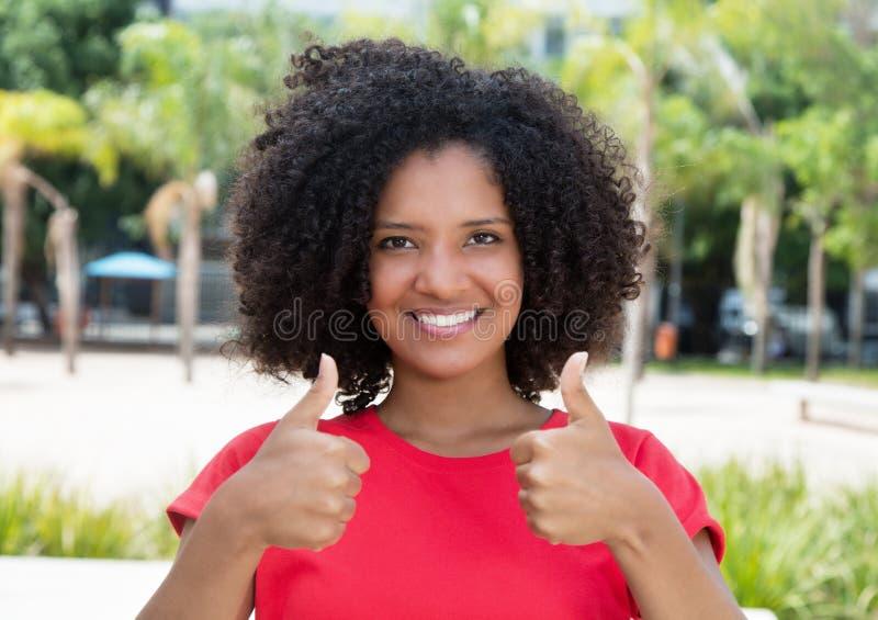 Adolescente afroamericano en la camisa roja que muestra ambos pulgares para arriba fotos de archivo