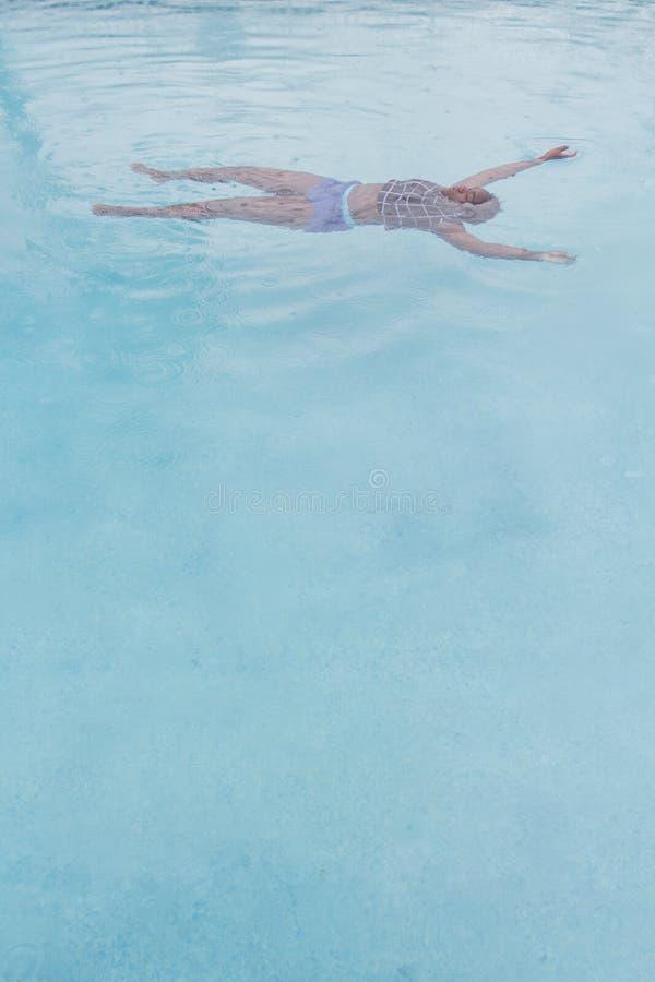 Adolescente afroamericano en la diversión de la natación de la piscina y de la lluvia foto de archivo