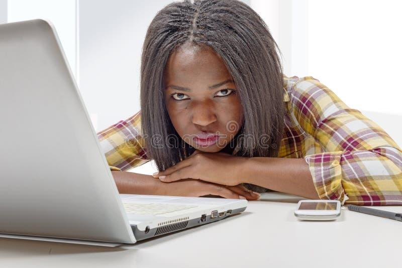 Adolescente afroamericano joven hermoso con el ordenador portátil imágenes de archivo libres de regalías