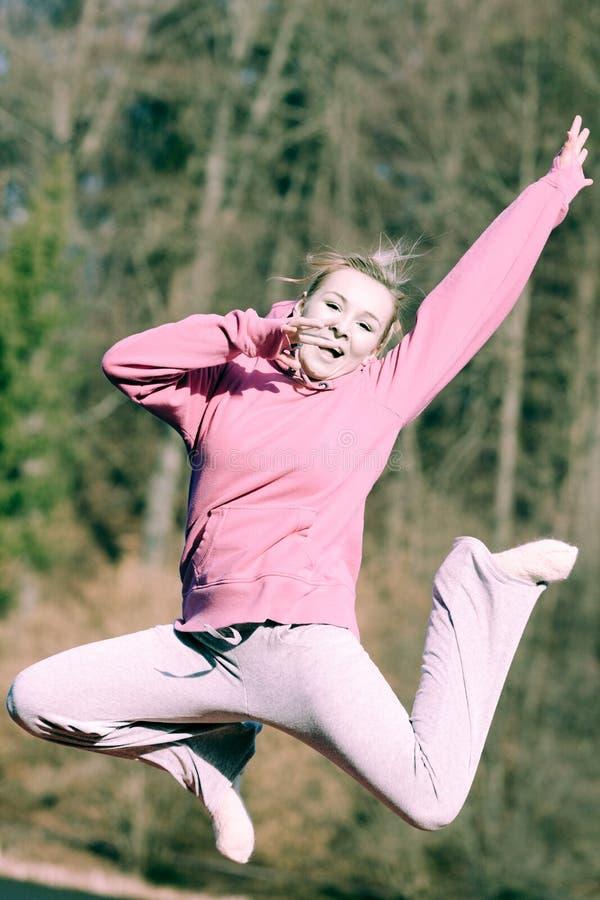 Adolescente alegre da mulher no salto cor-de-rosa do fato de esporte exterior fotografia de stock royalty free