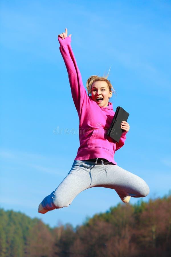 Adolescente alegre da mulher que salta com a tabuleta exterior foto de stock royalty free