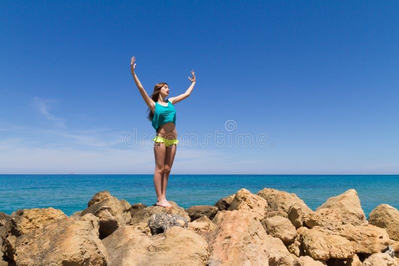 Adolescente alegre moreno en ropa de playa goza de foto de archivo libre de regalías
