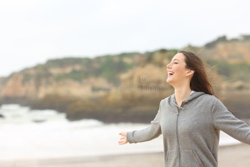Adolescente alegre que estica os braços na praia foto de stock