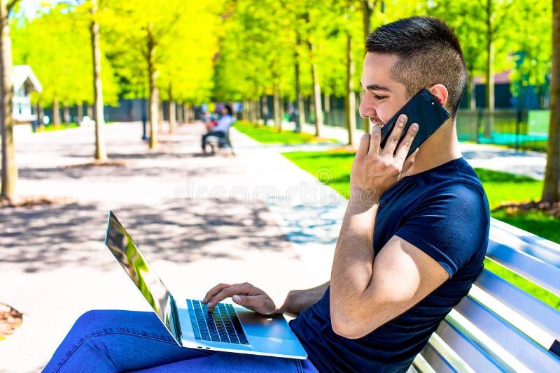 Adolescente alegre que llama vía el teléfono móvil y que usa el netbook, descansando al aire libre en parque de la ciudad en vera fotos de archivo