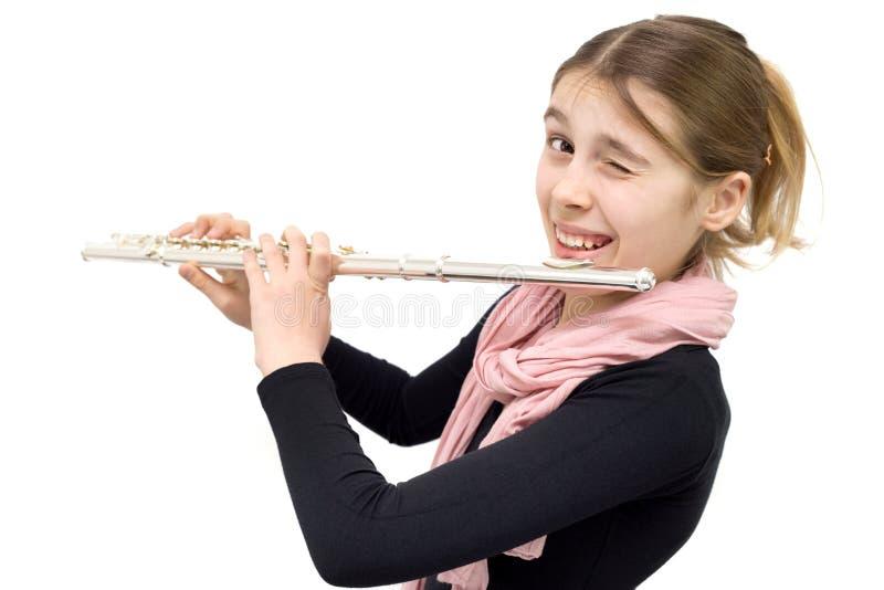 Adolescente alegre que sostiene la flauta y que guiña en la cámara aislada en blanco imagenes de archivo