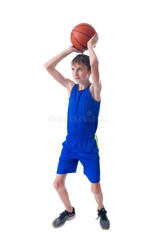 Adolescente alegre que sostiene una bola para el baloncesto sobre su cabeza Es imagen de archivo