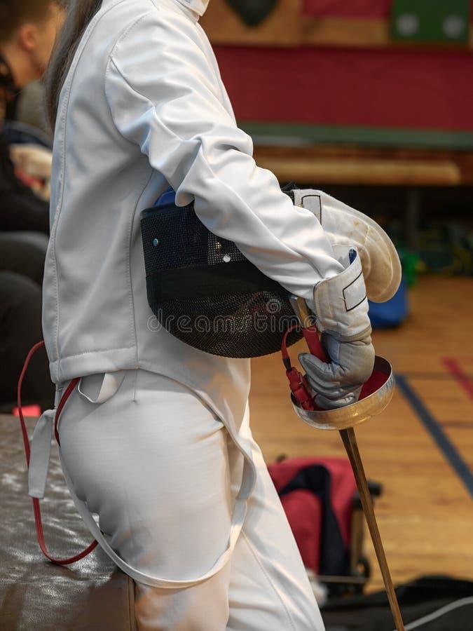 Adolescente alla concorrenza di recinzione con una spada e una maschera immagine stock