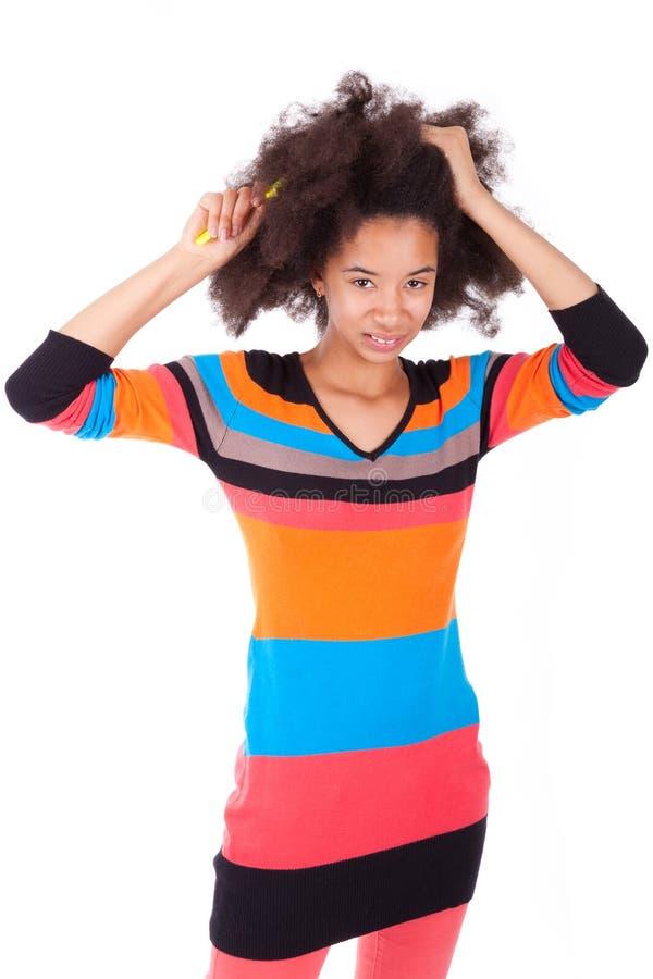 Adolescente américaine d'Africain noir se peignant les cheveux Afro image libre de droits