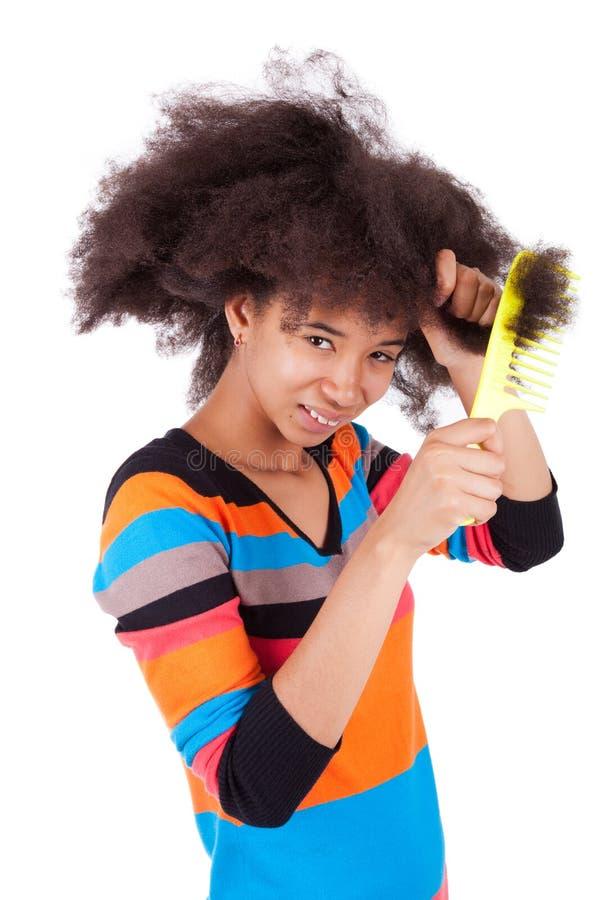 Adolescente américaine d'Africain noir se peignant les cheveux Afro photos libres de droits