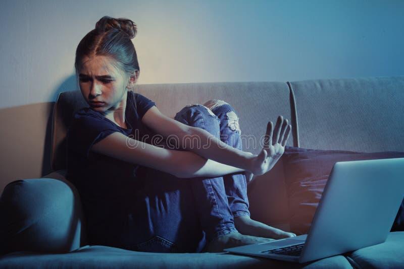 Adolescente amedrontado com o portátil no sofá Perigo do Internet fotografia de stock royalty free