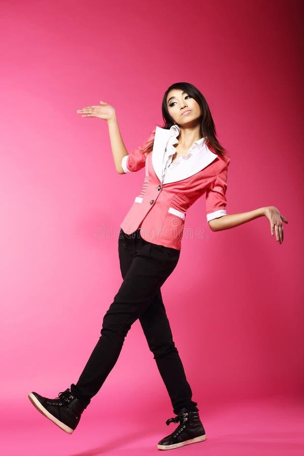 Adolescente amusing asiático que anda no estúdio cor-de-rosa foto de stock
