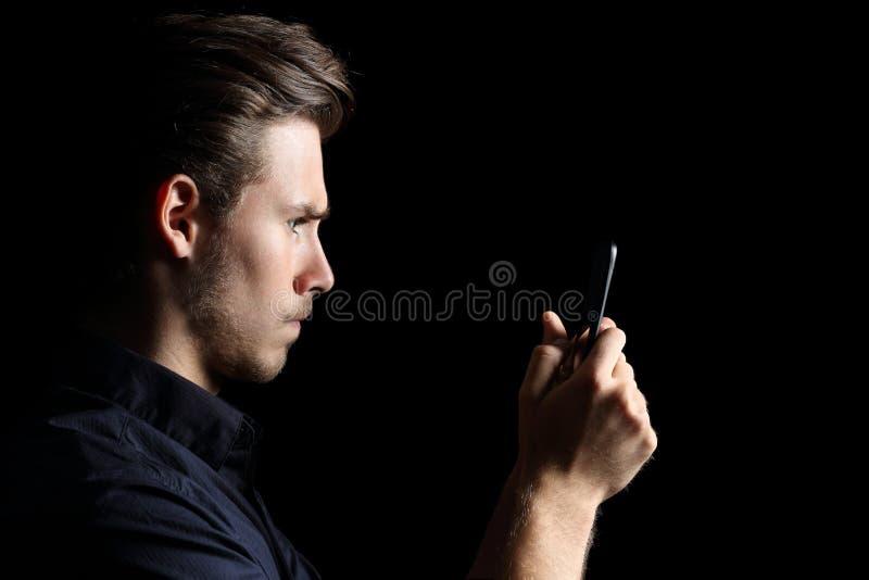 Adolescente andry obsesionado que manda un SMS en el teléfono en negro fotografía de archivo libre de regalías
