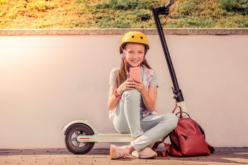 Adolescente apuesto sonriente en el equipo ligero que se sienta en la vespa electrónica imagen de archivo libre de regalías